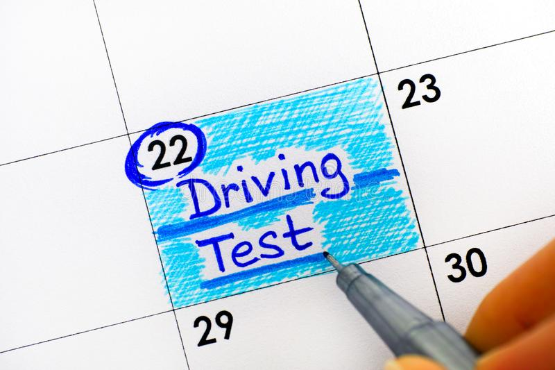 Woman fingers with pen writing reminder Driving Test in calendar. Close-up stock photography