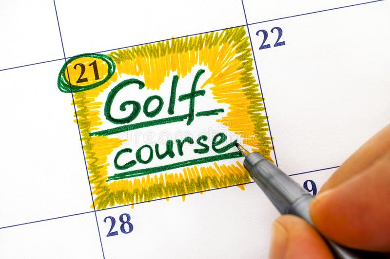 Woman fingers with pen writing reminder Golf course in calendar. royalty free stock photo