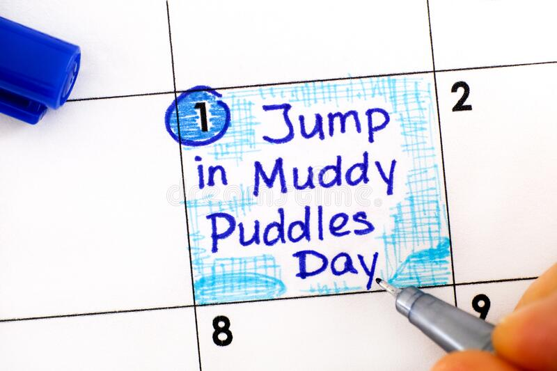 Woman fingers with pen writing reminder Jump in Muddy Puddles Day in calendar. April 01 royalty free stock photos