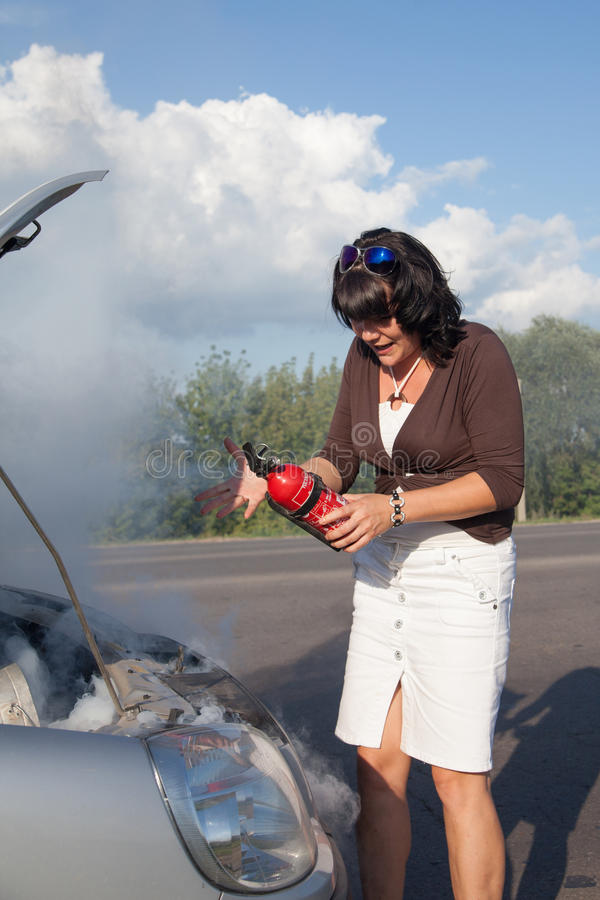 Woman with fire extinguisher. Near smoking car royalty free stock photography
