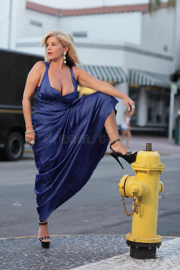 Woman by the fire hydrant. Woman with her leg posed on the fire hydrant royalty free stock photos
