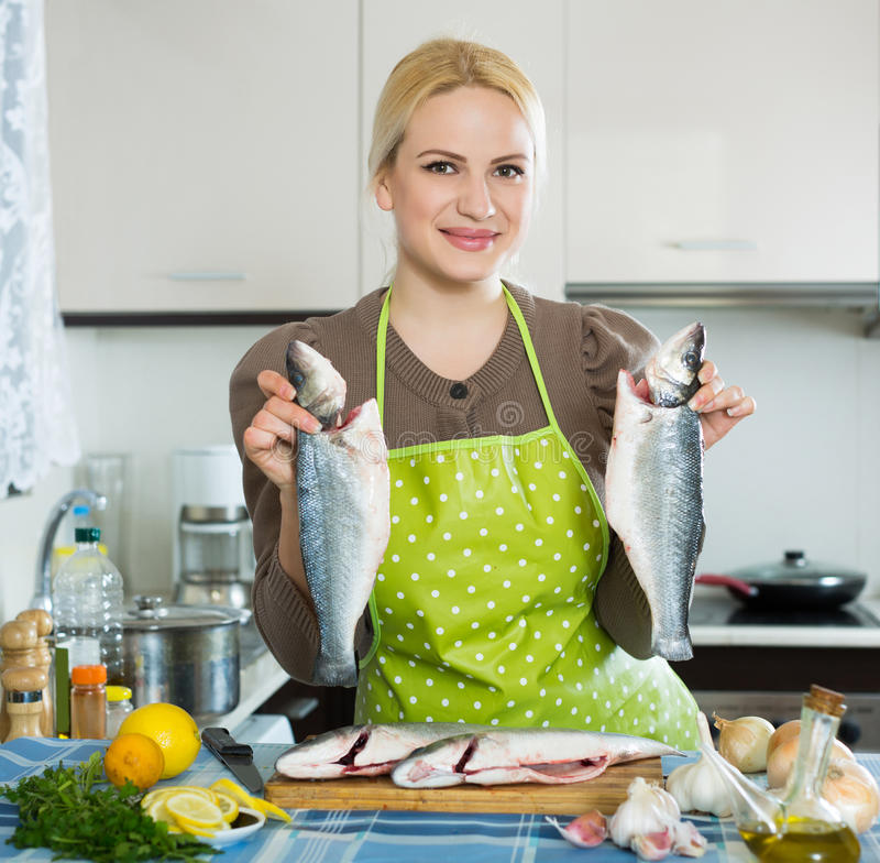 Woman with fish. Happy american woman with fish at home kitchen royalty free stock photo