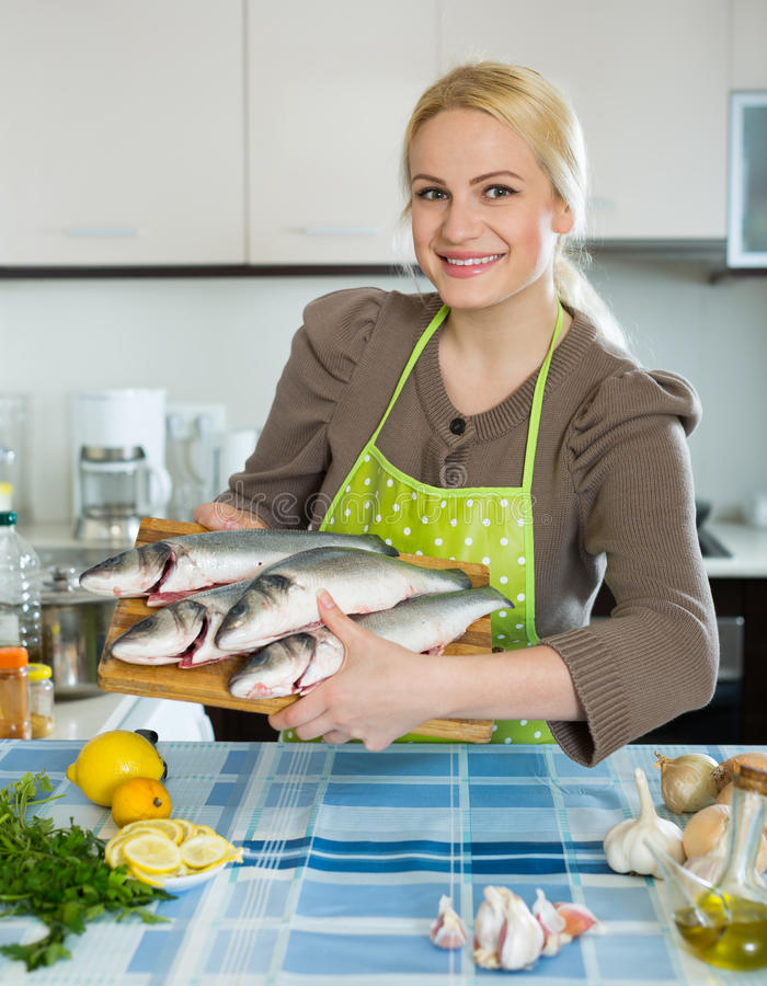 Woman with fish. Happy girl holding raw fish at the home kitchen royalty free stock photo
