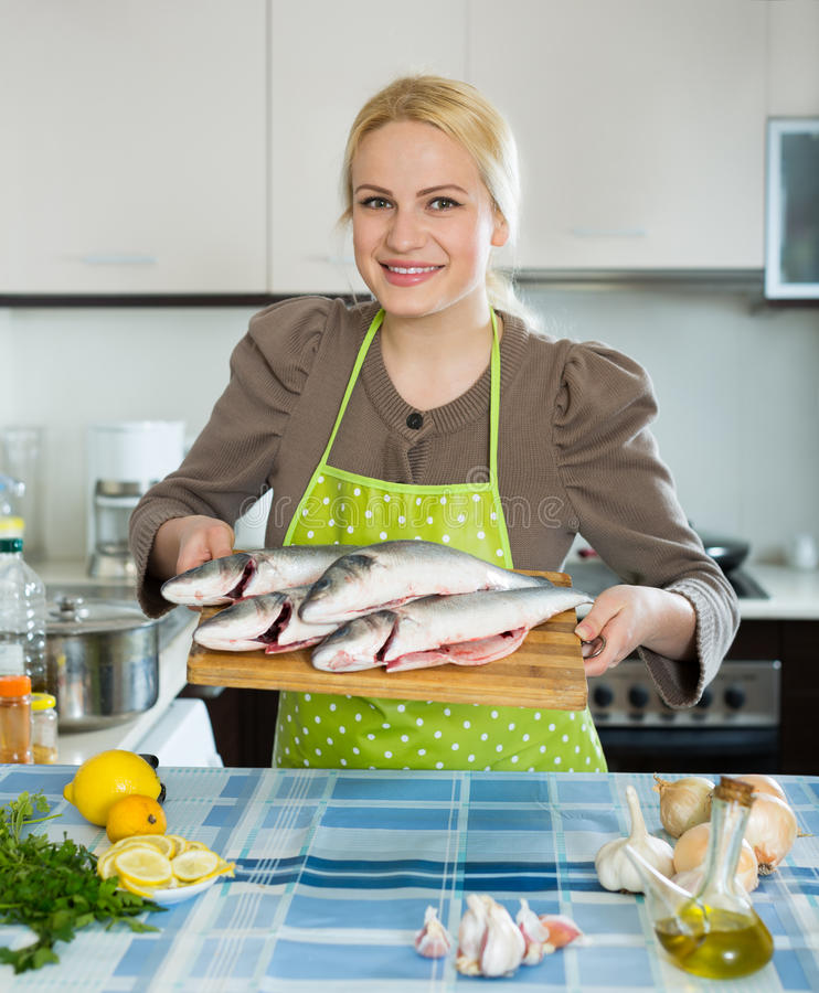 Woman with fish. Happy girl holding raw fish at home kitchen royalty free stock image