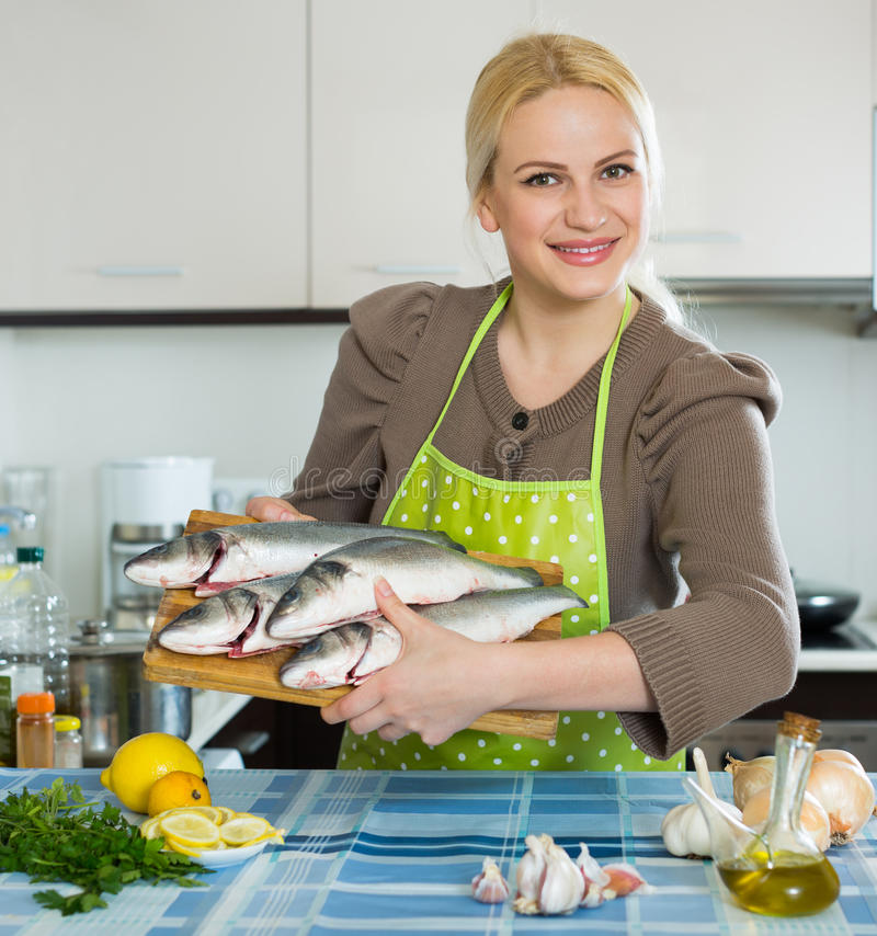 Woman with fish. Happy girl holding raw fish in home kitchen stock photography