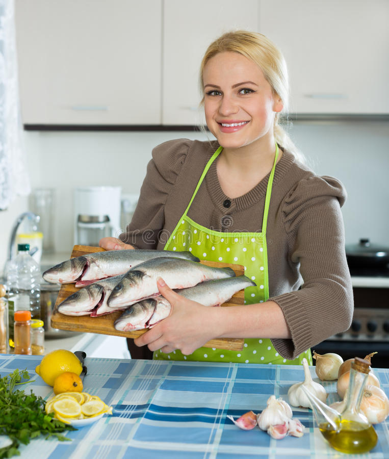 Woman with fish. Happy girl holding raw fish in the home kitchen stock images