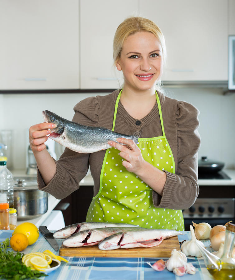 Woman with fish. Happy housewife cooking fish in home kitchen stock image