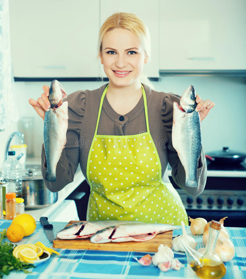 Woman with fish. Happy russian woman with fish at home kitchen royalty free stock photography