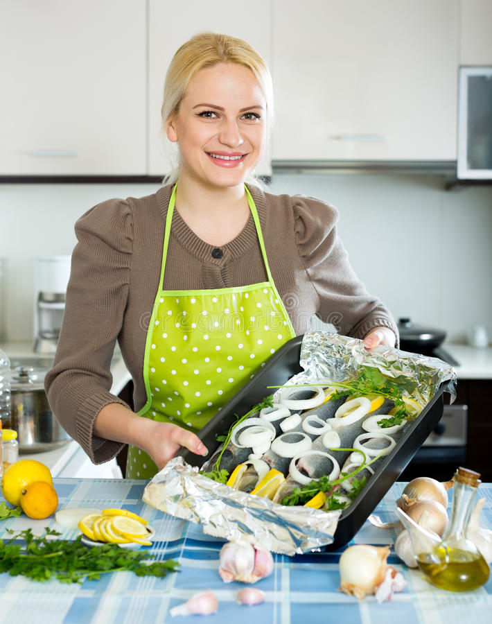Woman with fish in pan. Cheerful blonde girl cooking fish in frying pan at home kitchen royalty free stock images