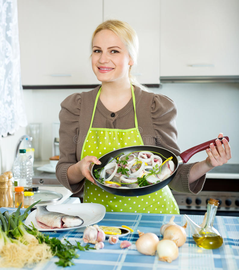 Woman with fish in pan. Happy woman cooking fish in frying pan at home kitchen stock photos