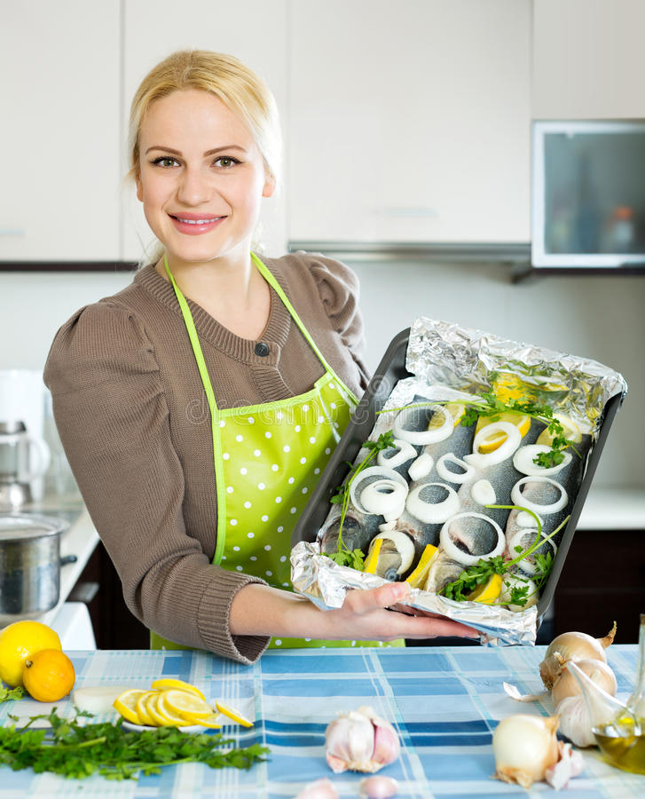 Woman with fish in pan. Smiling blonde woman cooking fish in frying pan at home kitchen stock images