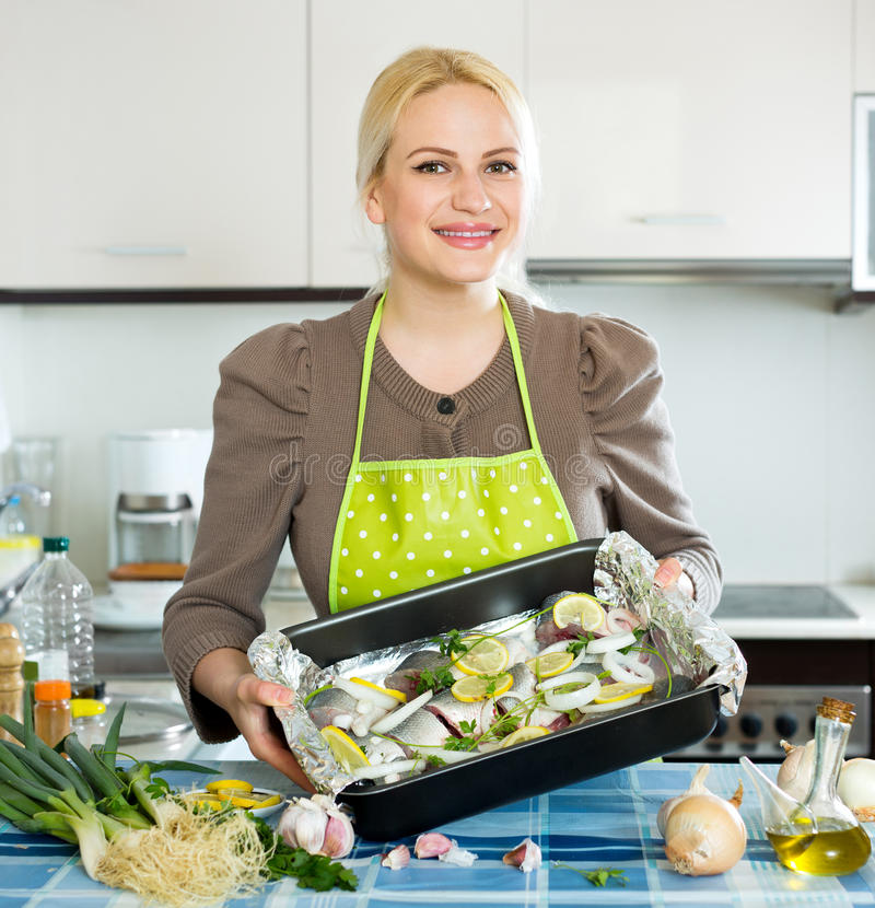 Woman with fish in pan. Smiling woman cooking fish in frying pan at home kitchen stock photos