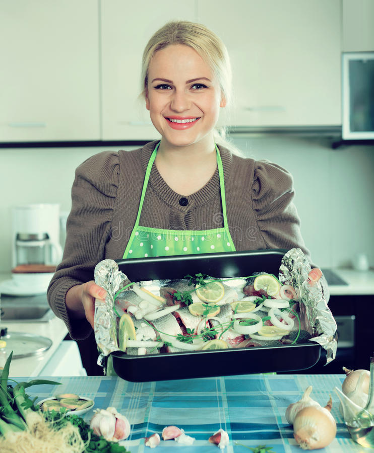 Woman with fish in pan. Smiling young woman cooking fish in frying pan at home kitchen stock image