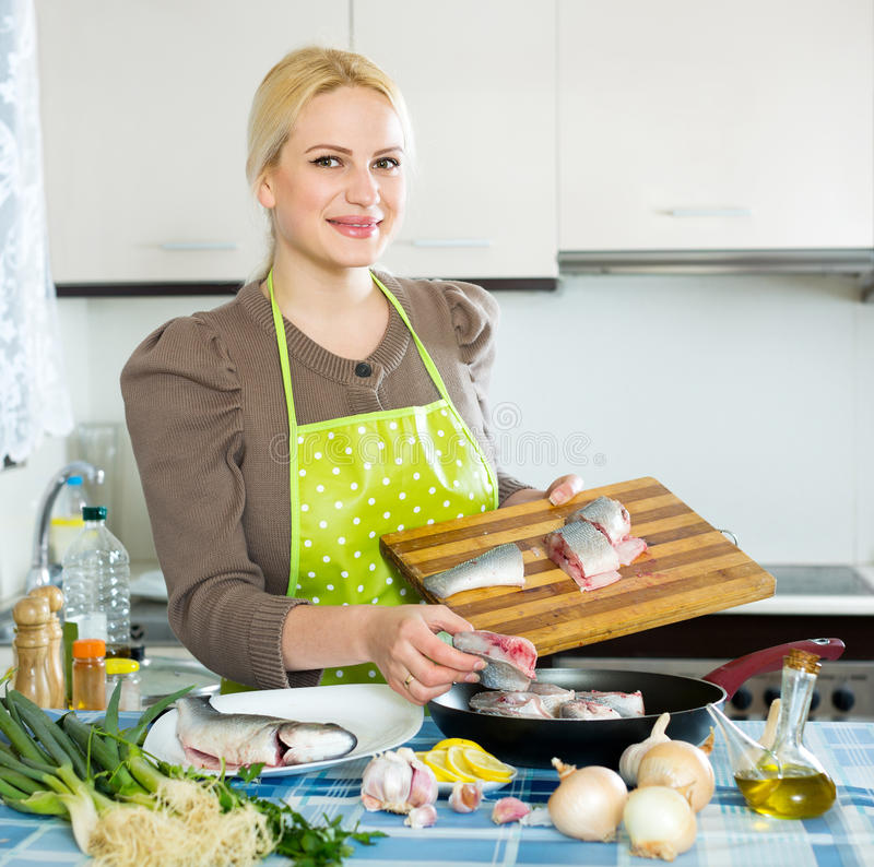 Woman with fish in pan. Young woman cooking fish in frying pan at home kitchen royalty free stock photo