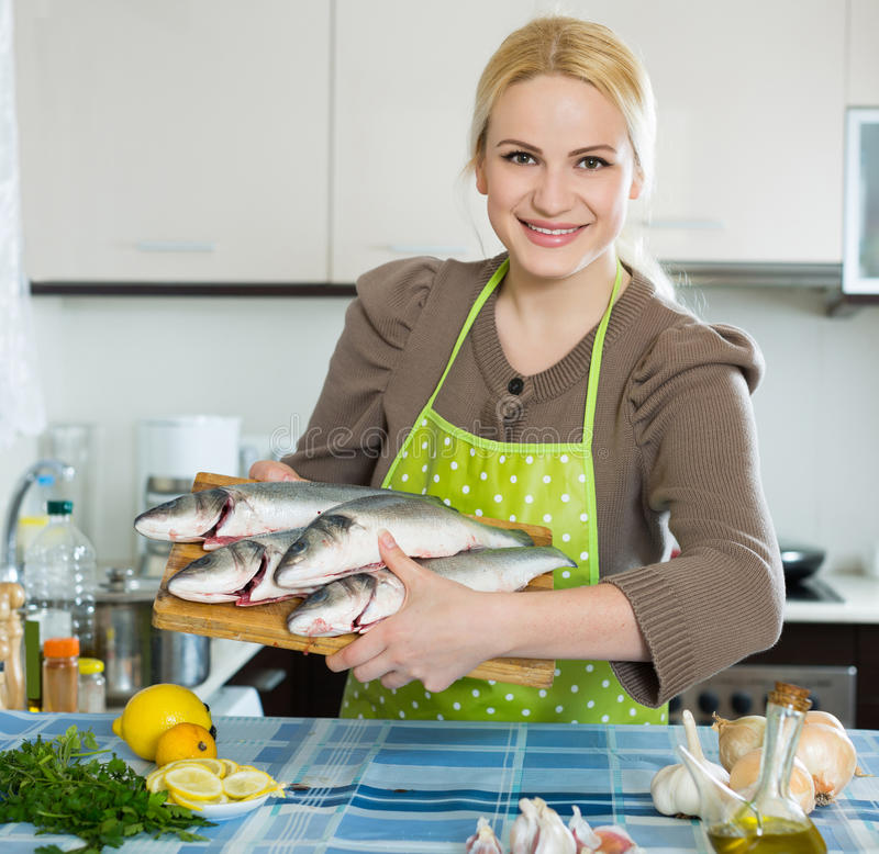 Woman with fish. Smiling american woman with fish at home kitchen stock photo