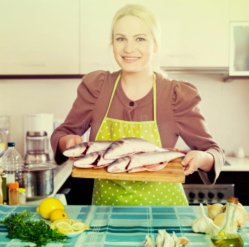 Woman with fish. Smiling german woman with fish at home kitchen royalty free stock image