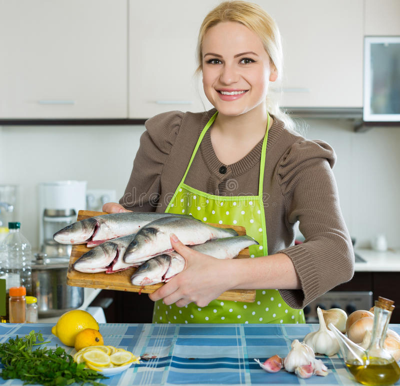 Woman with fish. Smiling woman with fish at home kitchen stock image