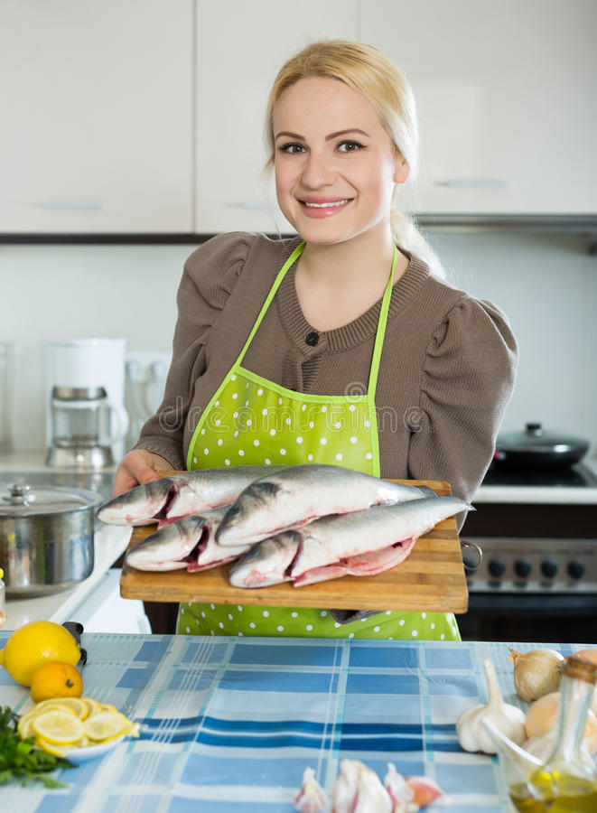 Woman with fish. Smiling russian woman with fish at home kitchen royalty free stock photography