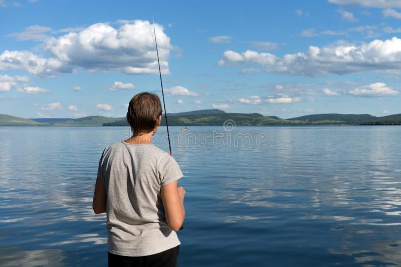 A woman fisherman stands with a fishing rod and catches fish against a blue lake and sky with clouds. Bright shot stock images
