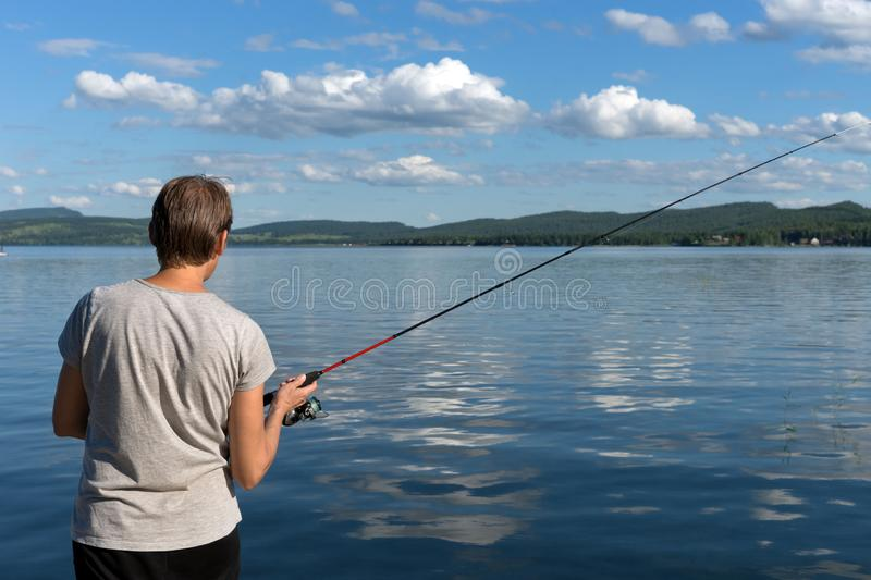 Woman is fishing from a beautiful blue lake against a mountainous shore and the sky with clouds. Bright shot stock photos