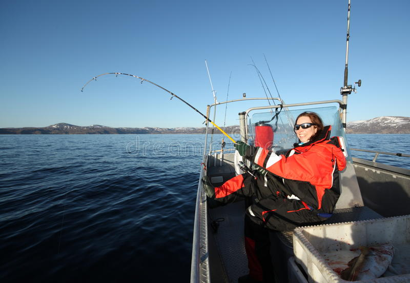 Woman fishing. Of the boat on the sea in Norway. Reeling up a big fish royalty free stock images