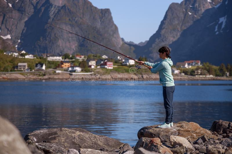 Woman fishing on Fishing rod spinning in Norway royalty free stock image