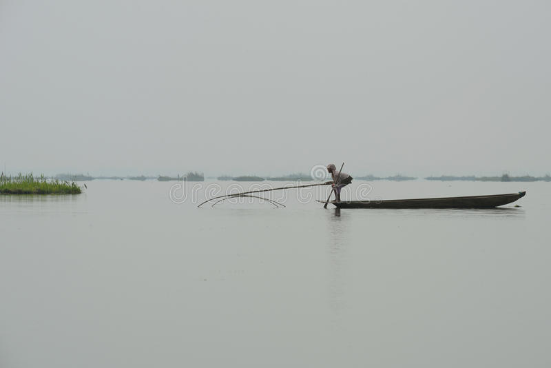 Woman fishing in lake with net stock images