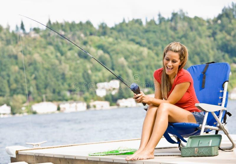 Woman fishing on pier stock image