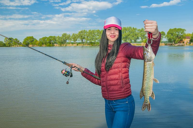 Woman on a fishing with pike fish trophy stock photo