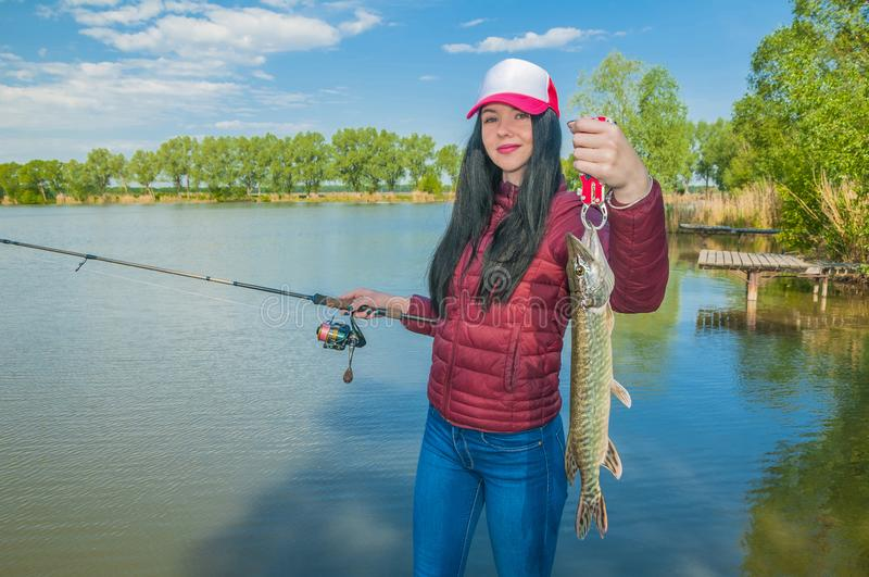 Woman on a fishing with pike fish  trophy stock photos