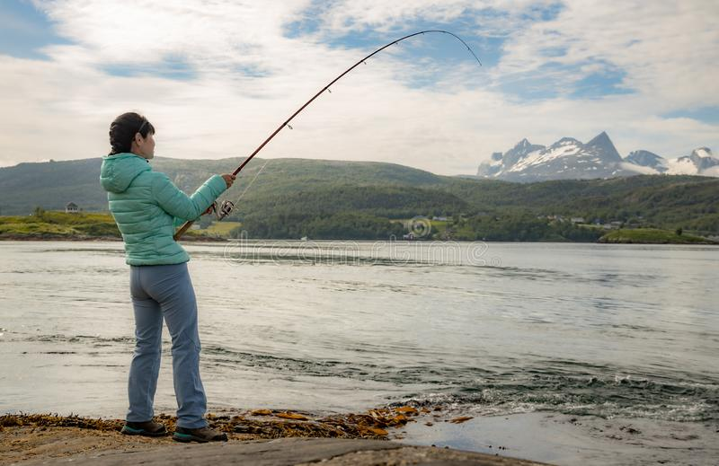 Woman fishing on Fishing rod spinning in Norway royalty free stock photography