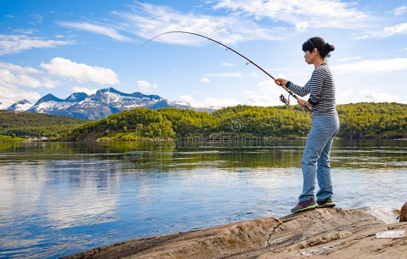 Woman fishing on Fishing rod spinning in Norway stock photos