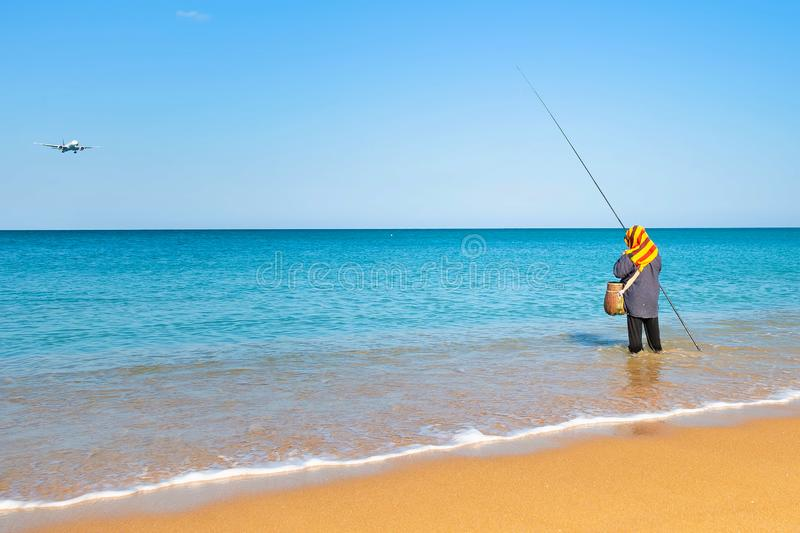 Woman fishing standing in the water near the shore. The sky is dropping the plane. Sunny clear morning on a tropical beach royalty free stock photography