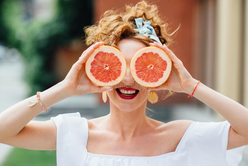 Woman fit girl holding two halfs of grapefruit royalty free stock photography