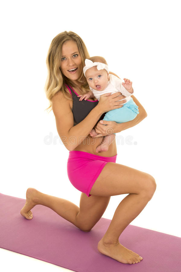 Woman in fitness attire lunge holding baby looking stock image