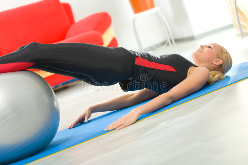 Woman with fitness ball. Young woman doing exercises with fitness ball at home royalty free stock image