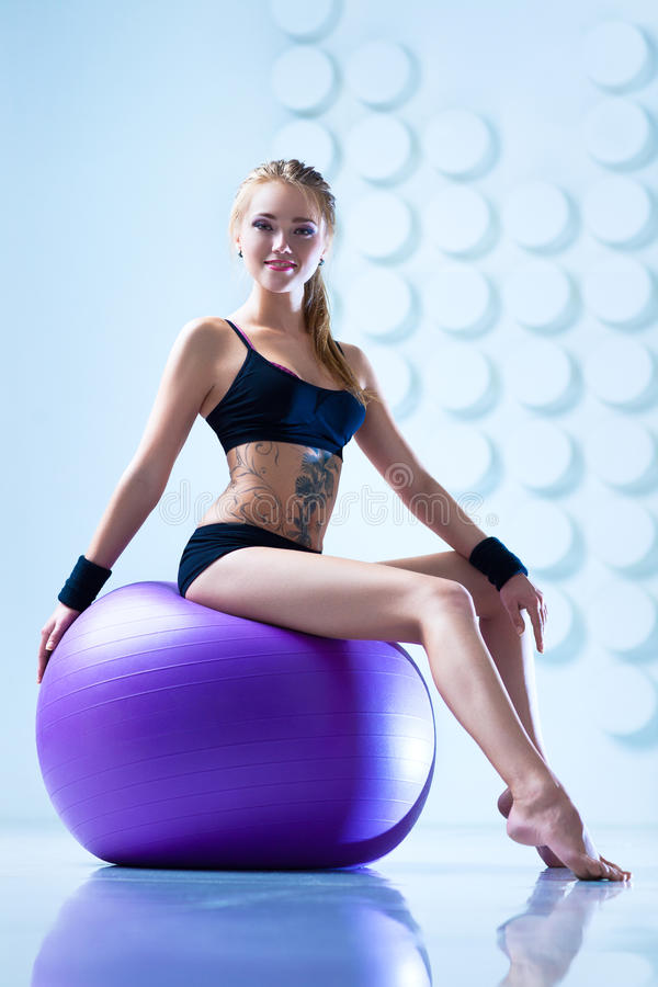 Woman with fitness ball. Young woman in black clothing with fitness ball in modern white interior. Tattoo on body stock photos