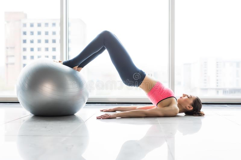 Woman and fitness ball. Young woman doing exercises with fit ball at gym. Woman is doing fitness at home on room floor near the wi stock image