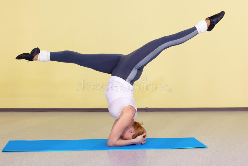 Woman on fitness carpet. Indoor portrait of woman training in gym on fitness carpet stock photo