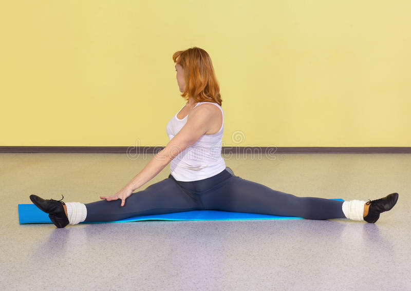 Woman on fitness carpet. Indoor portrait of woman training in gym on fitness carpet stock photography