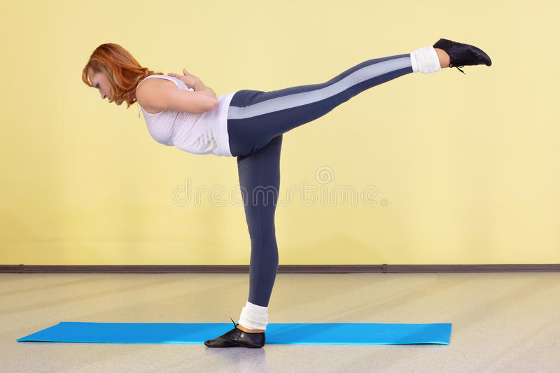 Woman on fitness carpet. Indoor portrait of woman training in gym on fitness carpet royalty free stock image