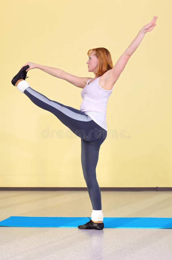 Woman on fitness carpet. Indoor portrait of woman training in gym on fitness carpet stock image