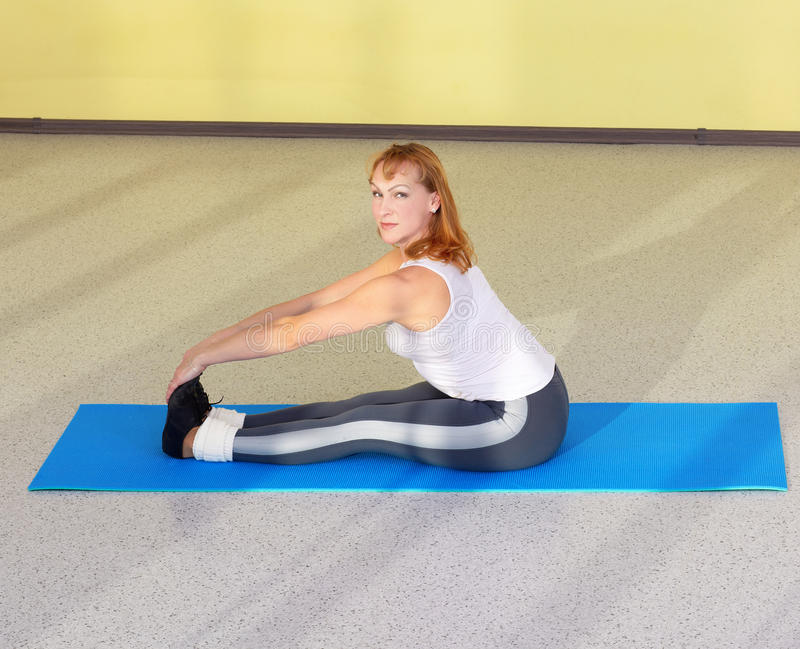 Woman on fitness carpet. Indoor portrait of woman training in gym on fitness carpet stock images