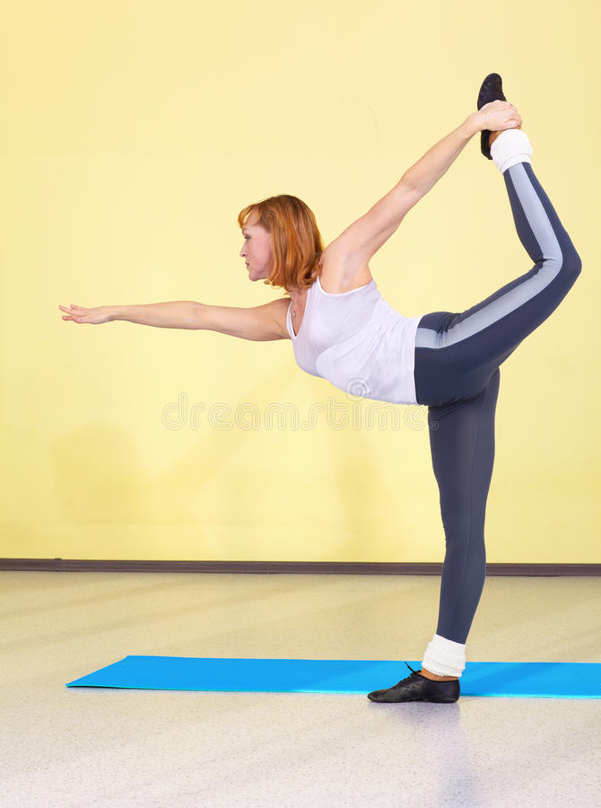 Woman on fitness carpet. Indoor portrait of woman training in gym on fitness carpet royalty free stock photos