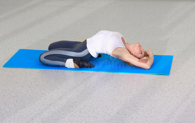 Woman on fitness carpet. Indoor portrait of woman training in gym on fitness carpet royalty free stock photo