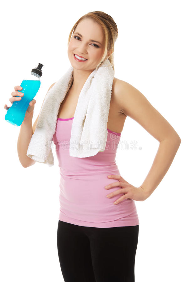 Woman in fitness clothes drinking isotonic drink. Attractive woman in fitness clothes drinking isotonic drink stock photography