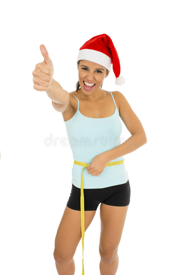 Woman in fitness clothes and santa Christmas hat holding measure tape on body waist. Young attractive latin sport woman in fitness clothes and santa claus royalty free stock photos