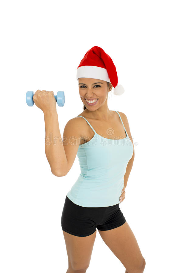Woman in fitness clothes and santa claus Christmas hat holding weight dumbbells stock photography