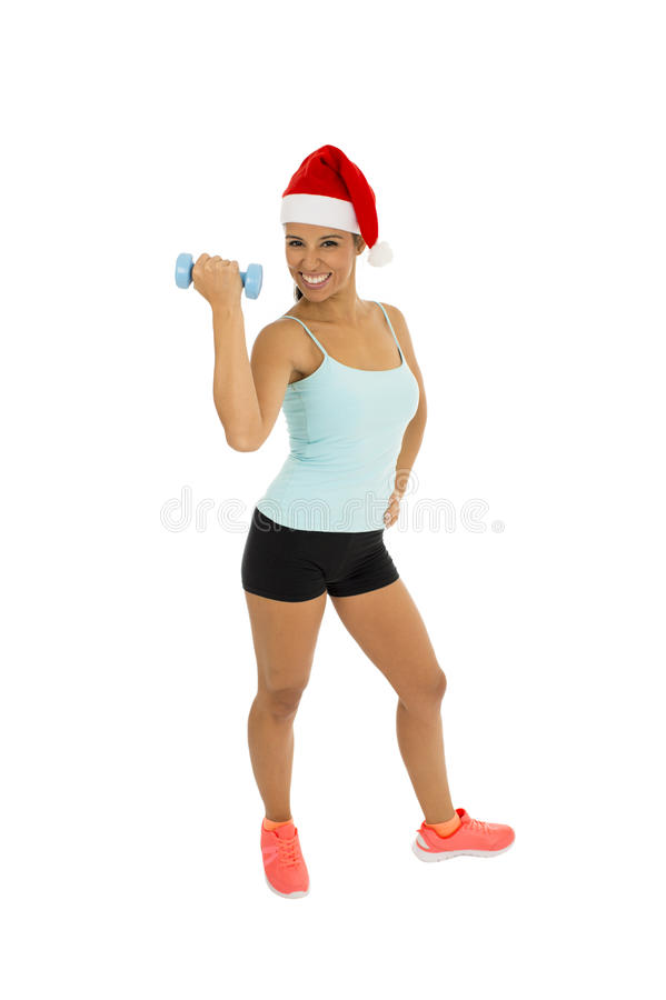 Woman in fitness clothes and santa claus Christmas hat holding weight dumbbells royalty free stock photo