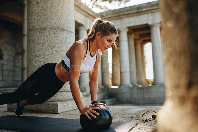 Fitness woman doing push ups using a medicine ball royalty free stock photos
